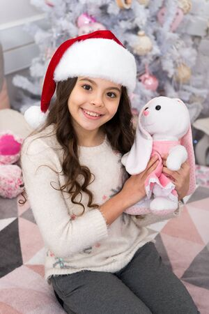 New year holiday. Small child wear santa hat celebrate new year at home decorated interior. Morning before christmas. Girl kid in bedroom with toys. Happy new year. Ask if the person has a wish list