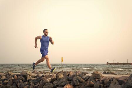 La douleur n'est rien comparée à ce que l'on ressent lorsqu'on arrête de fumer. Homme qui court sur la plage. Coureur s'entraînant à l'extérieur. Fit fitness sport masculin exerçant en été. Sport de course et passe-temps. Entraîneur de fitness homme