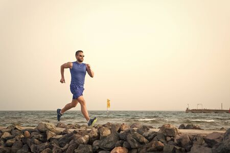Pain is nothing compared to what it feels like to quit. Running man on beach. Runner training outdoors. Fit male sport fitness exercising in summer. Running sport and hobby. Man fitness coach 版權商用圖片
