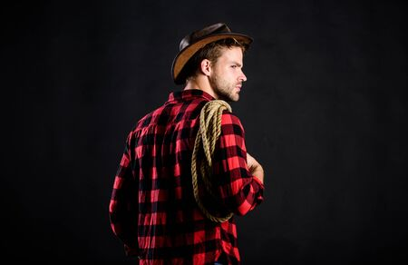 countryside. Vintage style man. Wild West retro cowboy. cowboy with lasso rope. Western. man checkered shirt on ranch. western cowboy portrait. wild west rodeo. man in hat black background