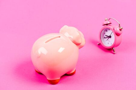 It is time to pay. Piggy bank pink pig and little alarm clock. Financial crisis. Economics and finance. Banking account. Bankruptcy and debt. Pay for debt. Bank collector service. Credit debt.