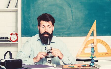 School teacher looking microscope. Fascinating research. Set up microscope. Teacher sit desk with microscope. Man bearded hipster classroom chalkboard background busy with biological observation Reklamní fotografie