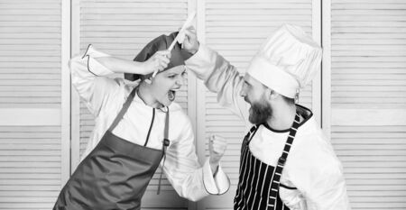 Cooking with your spouse can strengthen relationships. Ultimate cooking challenge. Couple compete in culinary arts. Woman and bearded man culinary partners. Reasons why couples cooking together 写真素材