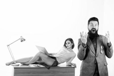 Bad news. Angry businessman shouting at secretary lying on desktop. Bearded man with open mouth on angry face. Hipster being angry about business problems. Feeling angry