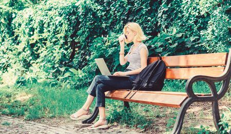 Woman student work with notebook. Learn study explore. Surfing internet. Modern student life. Regular student. Girl adorable student with laptop and coffee cup sit bench in park. Study outdoors