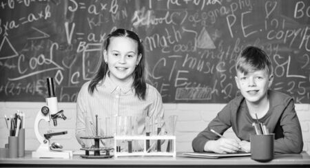 School laboratory. Girl and boy smart students conduct school experiment. Describe chemical reaction notepad. School education. Chemical analysis. Kids busy study chemistry. School chemistry lesson Reklamní fotografie