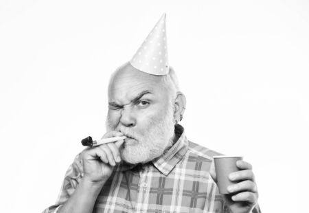 Grandfather graybeard blowing party whistle. Getting older is still fun. Elderly people. Birthday concept. Ideas for seniors birthday celebrations. Man bearded grandpa with birthday cap and drink cup Stok Fotoğraf