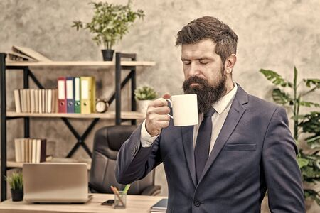Drinking coffee relaxing break. Boss enjoying energy drink. Start day with coffee. Successful people drink coffee. Caffeine addicted. Man bearded businessman hold coffee cup stand office background