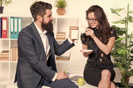 Keeping work and rest balance. Company managers drinking tea or coffee in rest hour. Coworkers enjoying short rest break at work. Pretty woman and bearded man having rest in office Reklamní fotografie