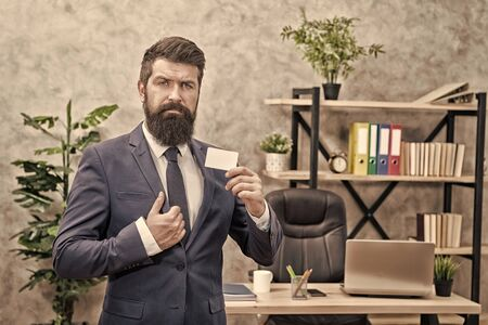 Banking services for small business. Card design. Call now. Guy formal suit stand in office. Accountant or banker. Businessman hold blank card. Useful contacts. Bearded hipster top manager show card 写真素材