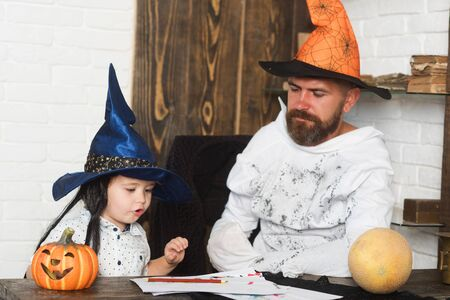 Man and kid with serious faces in witch hats