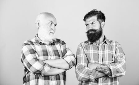 friendship. barbershop and hairdresser salon. father and son family. generational conflict. youth vs old age compare. retirement. male beard care. checkered fashion. two bearded men senior and mature 免版税图像
