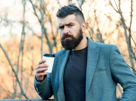 Caffeine gives him energy. Bearded man enjoy coffee in autumn morning. Businessman hold cup of hot energy drink. Being charged with energy