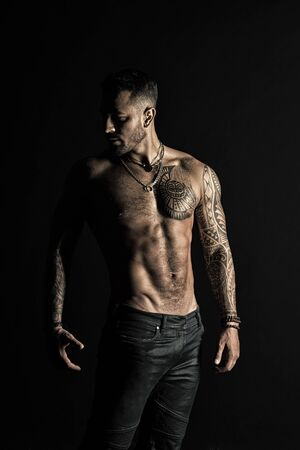 Fashion model with tattoo in jeans. Tattooed man show sexy muscular torso. Sportsman with six pack and ab. Bodybuilder with biceps and triceps. Bodycare with fitness and sport in vintage filter