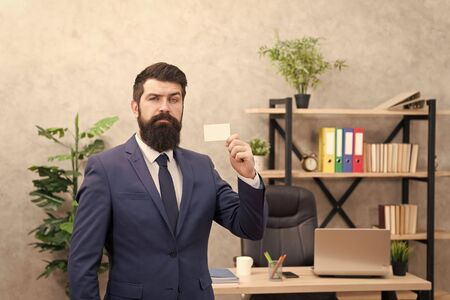 Useful contacts. Bearded hipster top manager show card. Banking services for small business. Card design. Call now. Guy formal suit stand in office. Accountant or banker. Businessman hold blank card 写真素材