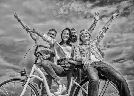 Firma stylowi młodzi ludzie spędzają wolny czas na zewnątrz na tle nieba. Rower jako część życia. Rowerowa nowoczesność i kultura narodowa. Przyjaciele z grupy spędzają czas z rowerem. Udostępnij rower na żywo przyjazny dla środowiska Zdjęcie Seryjne