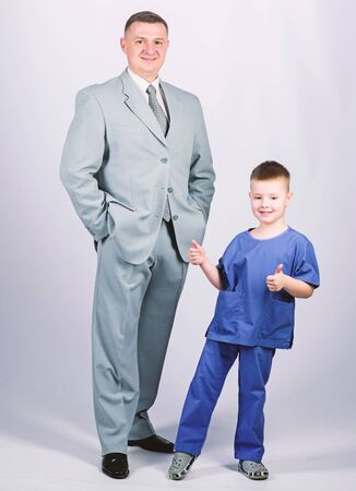 Dad boss. Father and cute small son. Child care development upbringing. Respectable profession. Man respectable businessman and little kid doctor uniform. Family business. Doctor respectable career Stock fotó