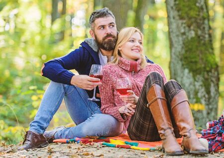 Table for two. couple in love relax in autumn forest. Family picnic. Valentines day. cheers. Red wine in fall weather. happy woman and bearded man drink wine. love date and romance. Spring mood