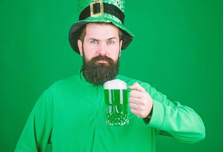 Lets get shamrocked. Bearded man toasting to saint patricks day. Irish man with beard drinking green beer. Hipster in green leprechaun hat holding beer mug. Celebrating saint patricks day in bar