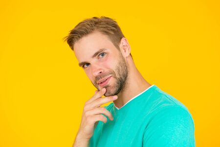 looking extraordinarily good. eyes like gimlets. handsome guy feel confidence. male facial care. having perfect look. sexy man beard yellow background. unshaven man touch chin. he has stylish bristle