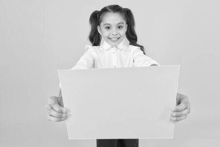 Eine Hausaufgabe bekommen. Kleines Kind, das leeres Blatt für Prüfungsarbeiten auf gelbem Hintergrund hält. Kleines Mädchen mit leerem Grünbuch für Projektarbeit oder Forschung. Papierkram, Textfreiraum