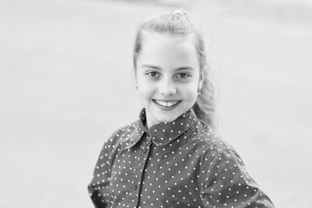 Belleza inocente de la niña. Chica feliz. Niña linda sonriendo al aire libre. Pequeña niña con cabello rubio y sonrisa adorable Foto de archivo