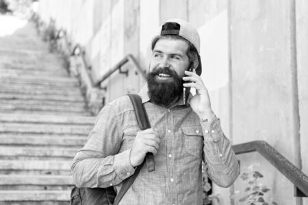 Happiness is traveling. Bearded man speak on phone. happy brutal man walk street. Male barber care. brutal hipster with backpack. hiking adventure concept. urban style. Mature hipster traveller