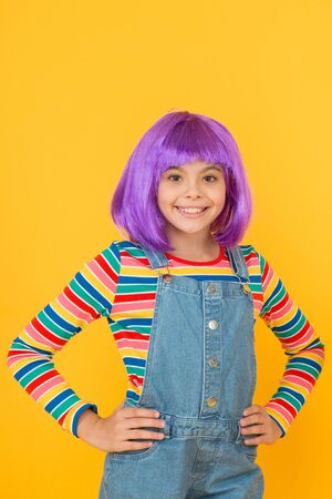 Cute is her mission. Happy child with cute smile yellow background. Cute little girl wear violet hair wig. Small fashion model with cute look. Cuteness is designed to appeal