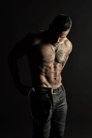 Sportsman with tattooed arm and chest. Bearded man shirtless with fit torso. Man with tattoo design on skin. Fashion model put leather belt on jeans. Bodycare with fitness and sport, vintage filter Stock Photo