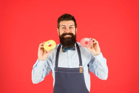 Doughnuts delivery. skilled baker with donut. funny hipster cook doughnut. temptation while diet. male cooking bakery. bearded man in chef apron. brutal waiter on kitchen. mature man red background Archivio Fotografico - 133758324