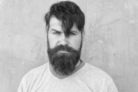 Bearded and shaggy. Bearded man with stylish haircut on grey wall. Unshaven caucasian guy wearing thick mustache and beard hair on bearded face. Brutal hipster in bearded style