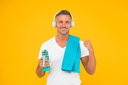 his morning begins from favorite music. full of energy. ready for new day. start day from sport training. fitness workout with good mood. sportsman guy yellow wall. happy man towel and water bottle