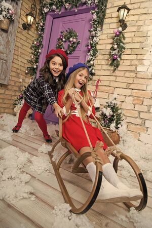 Child enjoy the holiday. The morning before Xmas. Little girls on sleigh. Christmas tree and presents. Christmas together. Happy new year. Winter. xmas online shopping. Family holiday