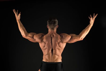 Increasing muscle mass through exercise. Muscle man back view on black background. Strong sportsman raising arms with triceps and biceps muscles. Fit bodybuilder showing muscle power
