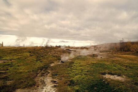Geyser natural miracle. Steam of hot mineral source in Iceland. Iceland famous for geysers. Iceland geyser park. Landscape meadow with clouds of steam. Geysir hot spring area. Highly active geyser