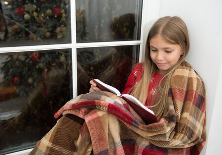 Magic xmas spirit. Little girl enjoy reading Christmas story. Little reader wrapped in plaid sit on window sill. Little child read book on Christmas eve. My favorite Christmas book Stock fotó