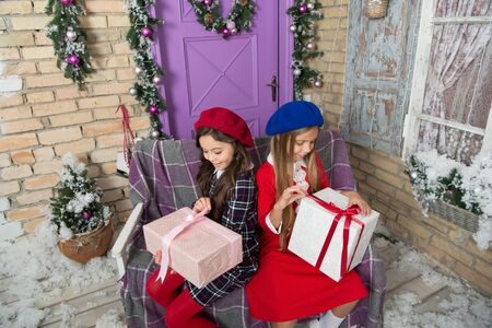 Unwrapping gifts on Christmas morning. Cute children open New Year presents. Happy little girls unwrap gift boxes. Merry Christmas and Happy New Year. Festive celebration of xmas and New Year at home