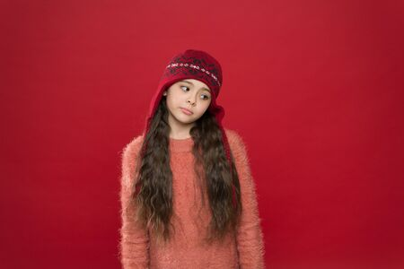 Feeling sorry. Little kid wear knitted hat. Stay warm. Little girl winter fashion accessory. Small adorable child long hair wear hat burgundy background. Cute model enjoy winter style. Winter outfit Stock fotó - 133871017