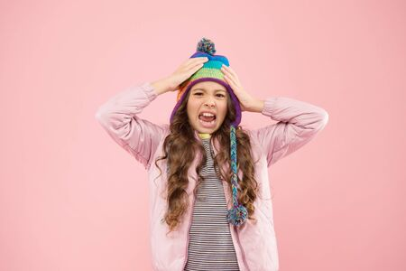 Preparing for winter. disgusted child pink background. kid fashion and shopping. girl. autumn style. happy childhood. small girl winter hat. ready for winter activity. warm clothes for cold season
