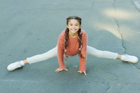 Pilates for health resolution. Small girl do splits outdoor. Little child enjoy pilates workout. Pilates stretching and flexibility exercises. Pilates or yoga for beginners Stock fotó