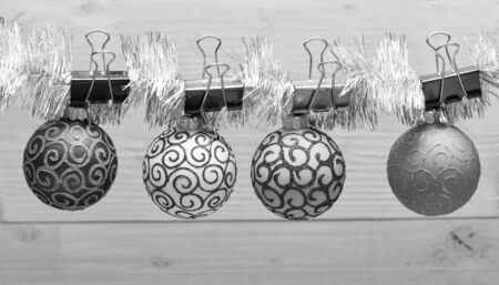 Tinsel with pinned christmas ornaments on wooden background. Christmas ornaments concept. Balls with ornaments hang on shimmering tinsel. Pick colorful decor for christmas tree. Stock fotó