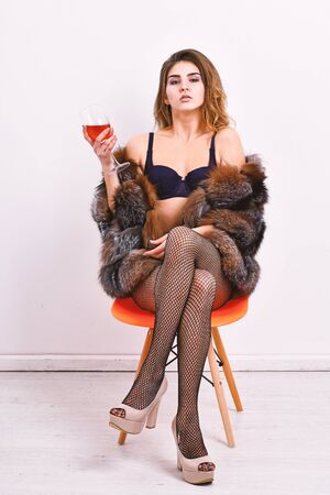 Girl you dream about. Fashion lady enjoy luxury lifestyle. Luxury life concept. Perfect woman luxurious appearance. Could be yours. Woman seductive model enjoy wine wear luxury fur and elite lingerie Banco de Imagens