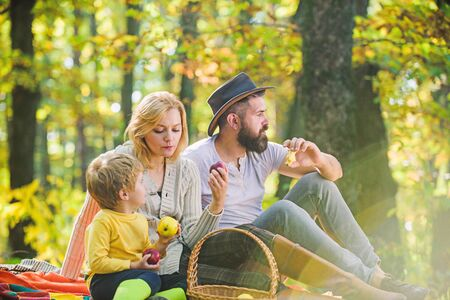 Spring mood. Happy family day. Sunny weather. Healthy food. Mother, cowboy father love their little boy child. Family picnic. Happy son with parents relax in autumn forest. Barbecuing to perfection Standard-Bild - 133950723