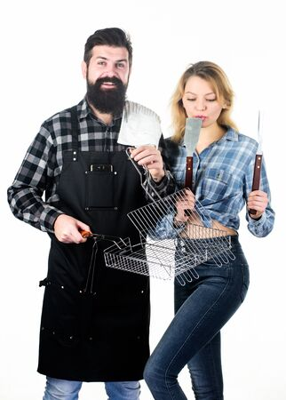 Couple in love hold cooking utensils for barbecue. Tools for roasting meat outdoors. Picnic and barbecue. Culinary concept. Man bearded hipster and girl ready for barbecue party. Family weekend Stock Photo