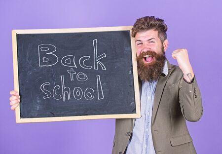 Continue your education with us. New semester in school. Teacher invites to continue studying. Teacher bearded man stands and holds blackboard with inscription back to school violet background