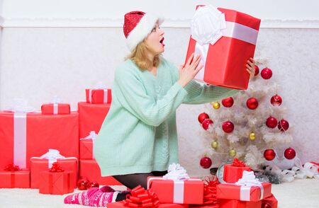 Opening christmas gift. Girl near christmas tree happy celebrate holiday. Perfect gift for girlfriend or wife. Give her gift that she always wanted. Woman excited blonde hold gift box with bow Stock Photo