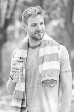Obey your thirst. Thirsty sportsman. Bearded man holding bottle of drinking water to quench his thirst. Thirst quenching during sports training or fitness activity outdoor. Thirst and dehydration
