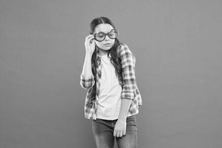 Fashionable cutie. Being smart. Little smart schoolgirl on orange background. Child smart look through eyeglasses. Small kid wearing eyeglasses smart style. School party concept. Sunglasses accessory