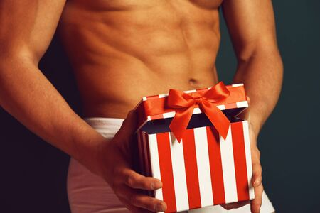 sexy macho man with sexy muscular athletic strong body has bare torso and strong belly holding colorful christmas or xmas present box. on green studio background Banco de Imagens