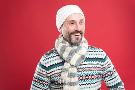 Menswear concept. Fashion collection. Fashion clothes. Knitted accessories. Cold winter conditions. Handsome bearded man wearing hat and scarf red background. Winter fashion. Winter weather style Banco de Imagens